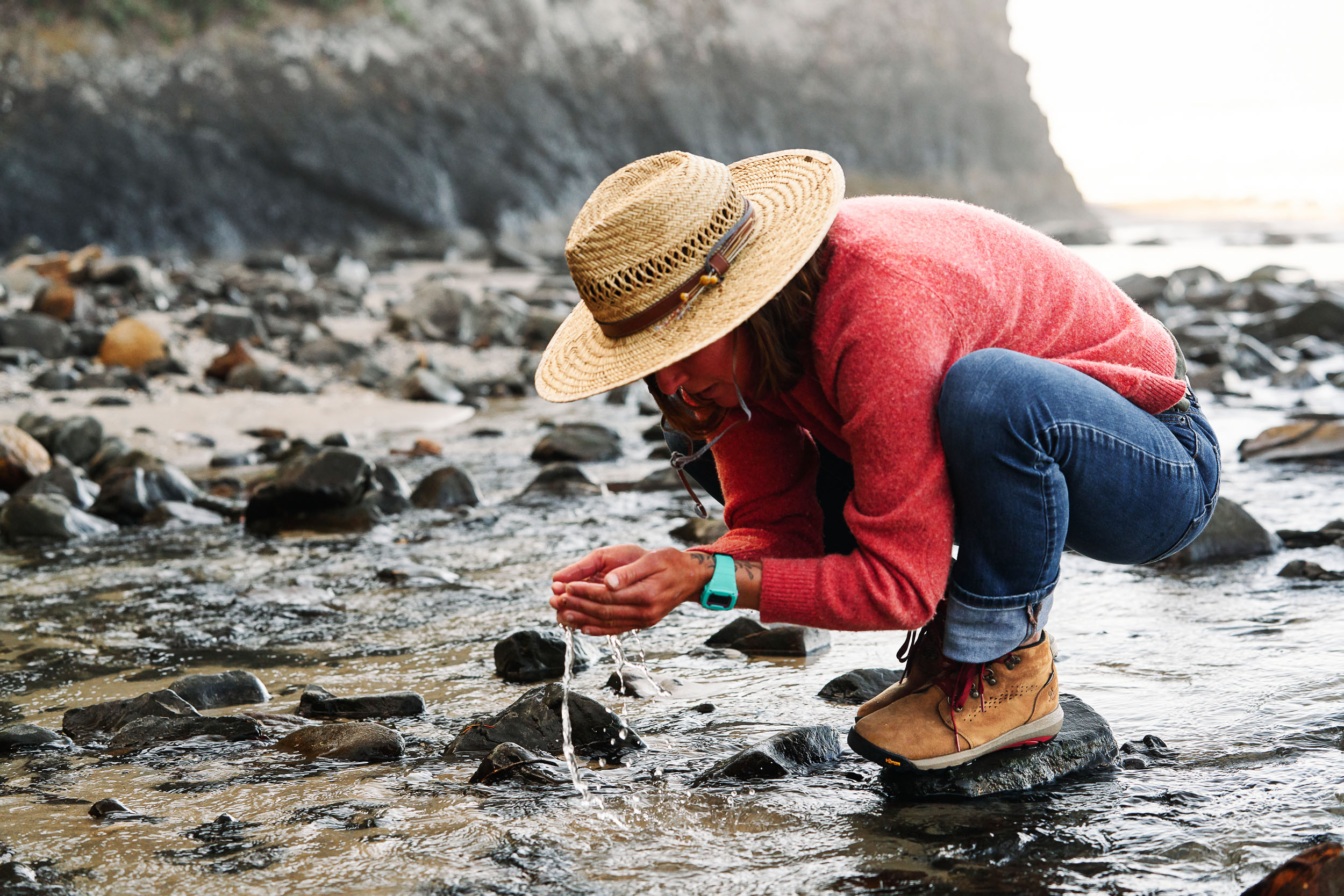 Lauren Ahlgren of Oregon Surf Adventures finding a cold drink of water while wearing Danner Inquire Boots on the Oregon Coast.